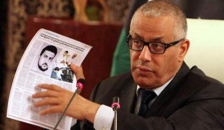 Libyan Prime Minister Ali Zidan holds up copies of foreign newspapers reporting the kidnapping of Abu Anas al-Libi by US special forces