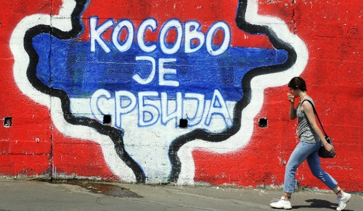 "A woman walks past a map of Kosovo painted on a wall, with the words ""Kosovo is Serbia"""